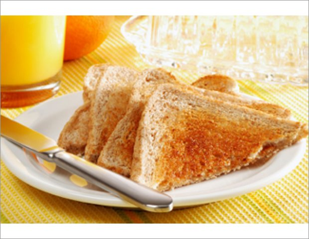 Breakfast with juice, coffee, toast, honey, butter and bread